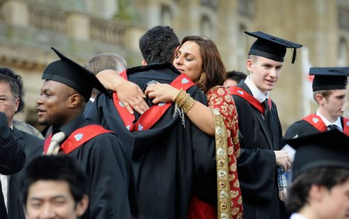 Photo of graduates being hugged by family members as university graduates celebrate their graduation day at a British University